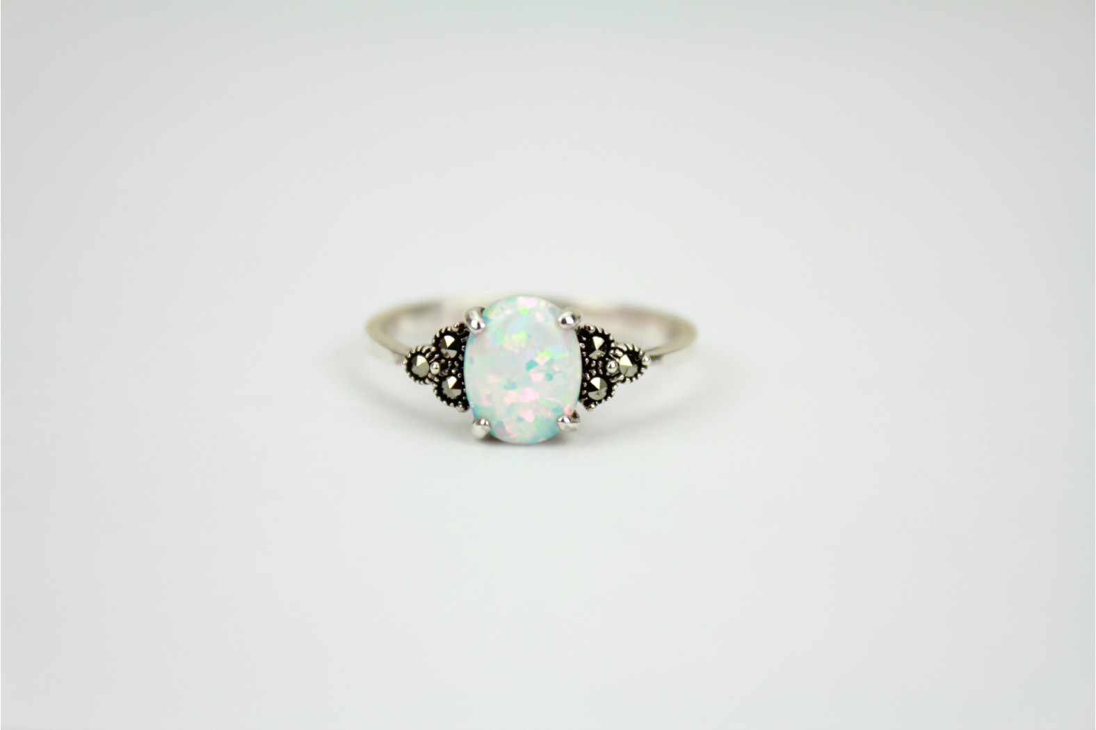Petite claw set oval shaped White Opal Fire with minimal Marcasite stones on shoulders. size 9 or R. TEMPORARILY OUT OF STOCK.