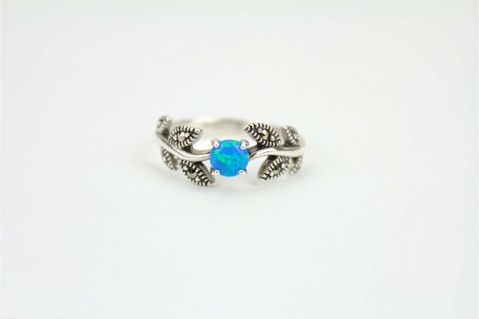 Stunning creation Blue Opal Fire with Marcasite stones set on vine leaf style detailing. Size 8 or P
