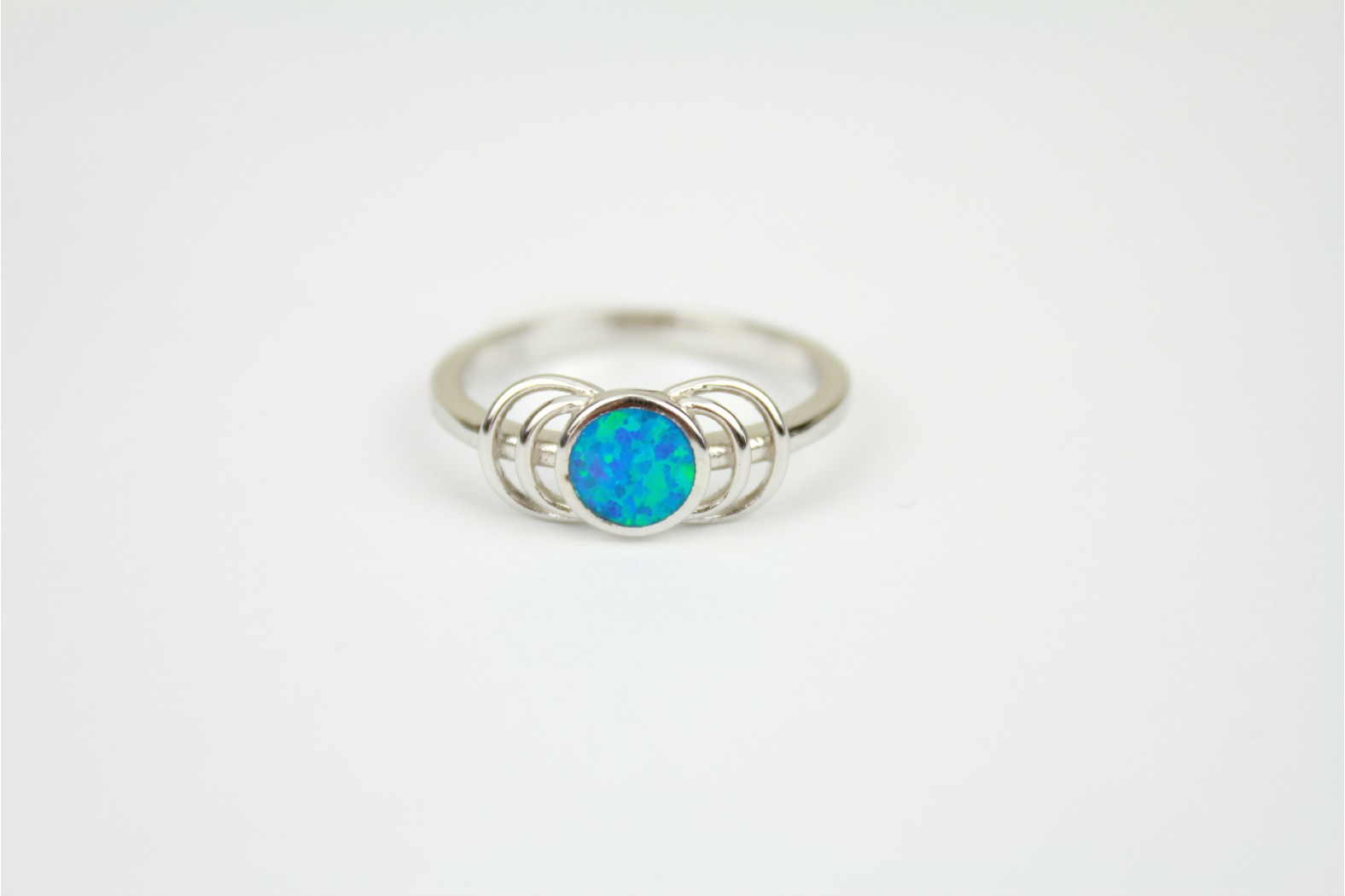 Round Blue Opal fire set on silver with swirling shoulder detailing size 9 or R
