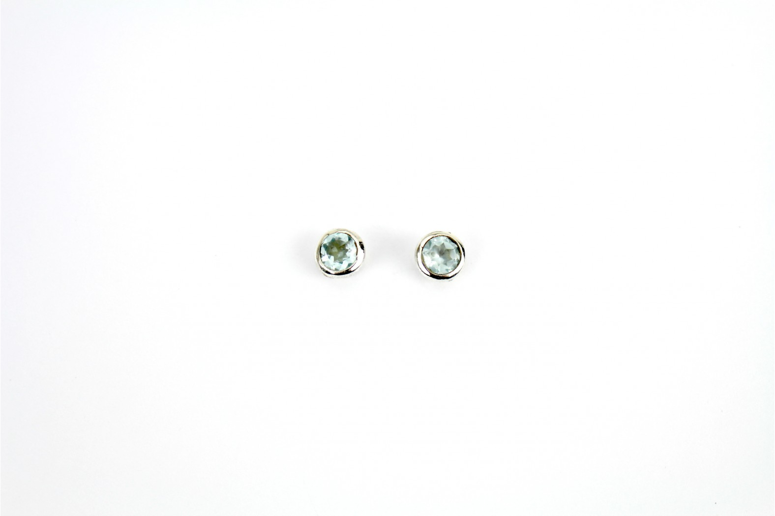 Circular Sky Blue Topaz stud earrings set in circular silver mounting